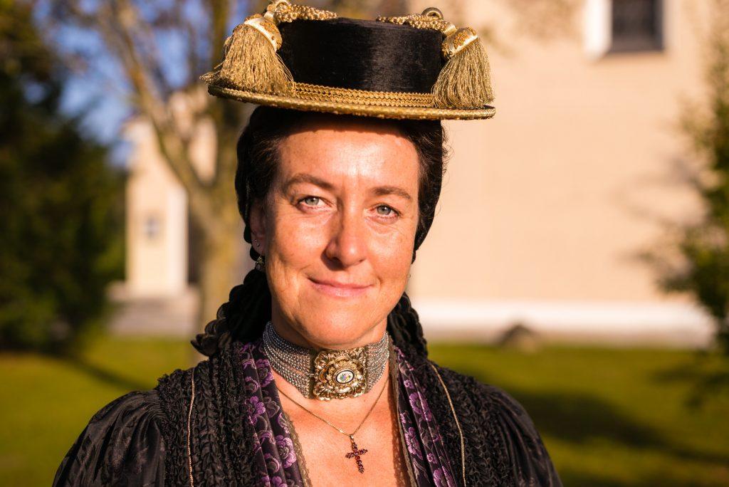 """Röckifrau Martina Schedl trägt einen Priener Hut mit 4 Quasten, einen dunklen Seidentuch-Einsatz im Oberteil wie er zu Traueranlässen getragen wird und eine wertvolle, alte """"Kropfkette"""", die von einem Kettenstrang mit 15 """"Gängen"""" (einzelne kleine Silberketten"""" gehalten wird."""