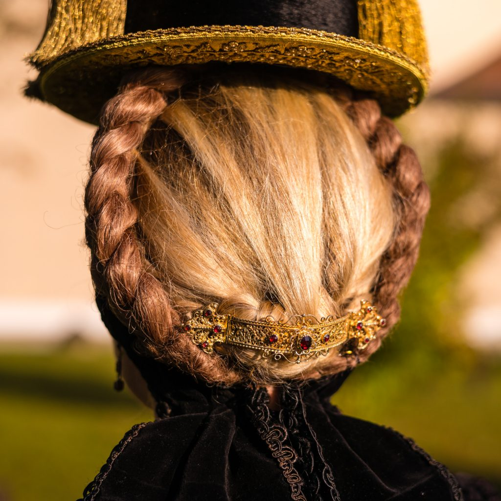 Röckifrau mit Gretl-Frisur, geschmückt mit filigraner, granatbesetzter Goldspange. Sie trägt den sog. Priener Hut, hier in einer Variante mit vier Goldquasten (beidseitiges Quastenpaar).