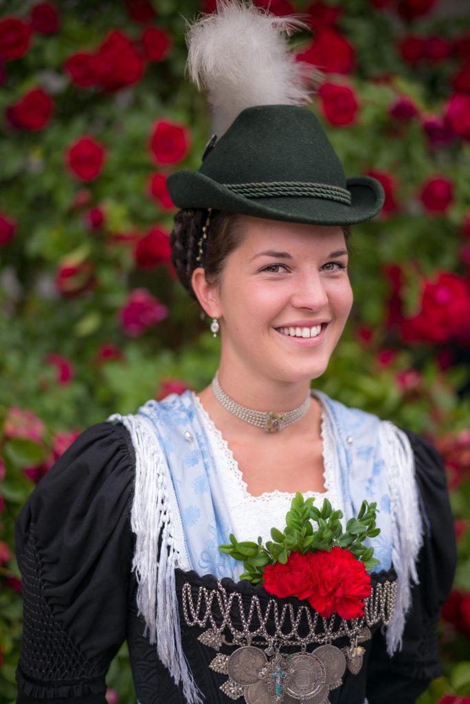 Regina Rauch in der Festtagstracht der Aktiven Dirndl mit Hut und Miederoberteil mit langem Ärmel-Einsatz.