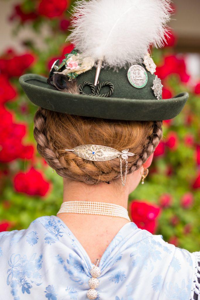 """Die Aktiven Dirndl tragen zur Festtagstracht einen Samt- oder Filzhut, der mit einem kleinen Adlerflaum geschmückt ist. Das Dirndl trägt eine """"Gretl-Frisur"""", hier mit schmückender Silber-Haarspange."""