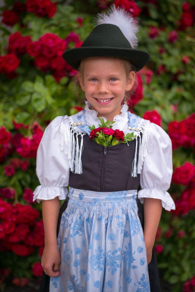 Dirndl aus der Kindergruppe in Festtagstracht mit Hut, Seidentuch und Seidenschürze