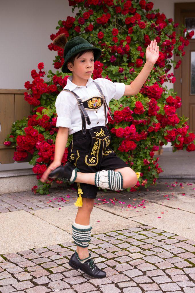 """""""Früh übt sich…"""" Bua aus der Atzinger Kindergruppe probt einen Schuhplattler vor dem Atzinger Vereinshaus. Auf die Ordnung bei seinen """"Loiferln"""", den handgestrickten und mit feinen Mustern besetzten grün-weißen Wadlstrümpfen, muss er noch ein wenig achten."""