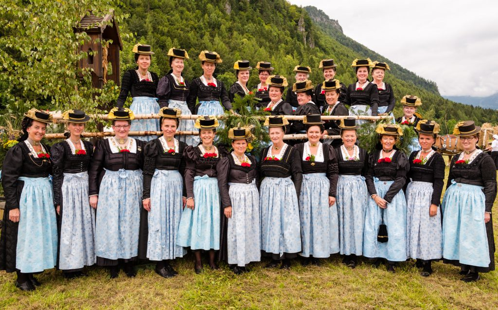Die Röckifrauen des Atzinger Trachtenvereins auf einer Aufnahme, die im Rahmen des Gautrachtenfestes in Unterwössen entstand. Die Frauen tragen die blauen Seidenschürzen und weiße, goldbestickte Einsätze im Oberteil.
