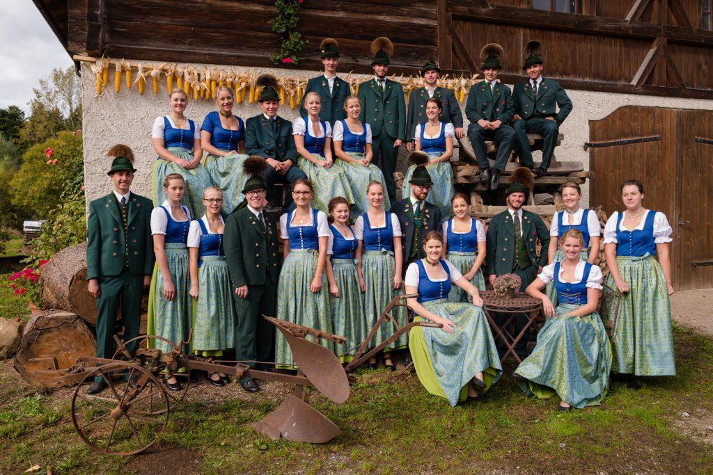 """Gruppenaufnahme der Aktiven am Stadl des """"Krughofs"""" in Mupferting. Die Buam tragen den """"Forstgrünen Anzug"""" mit Krawatte/Binder und """"Laibl"""" (Weste). Dieses sog. """"Greane Gwand""""– wie es zu sehr feierlichen Anlässen getragen."""