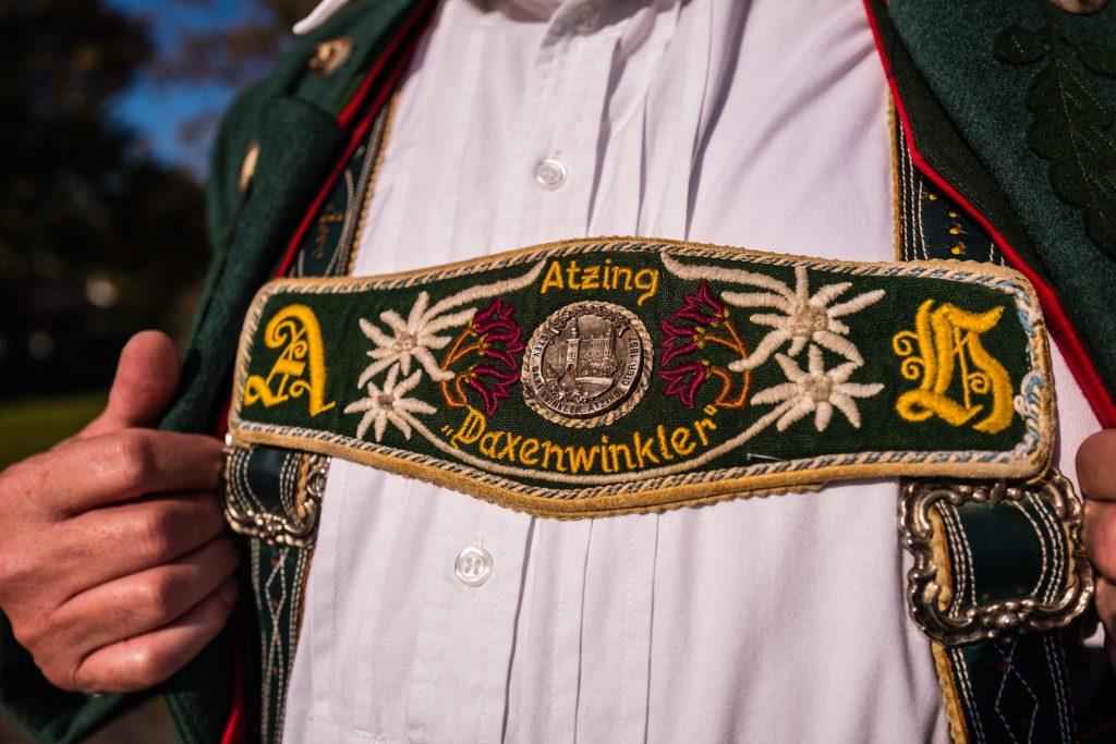 Seit 1987 einheitlicher Hosenträger der Atzinger Trachtler mit Initialen des Trägers, einem Schriftzug mit dem Vereinsnamen und einem Metall-Vereinsabzeichen.