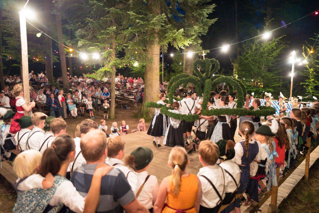 Stimmungsvolle Eindrücke von den alljährlich stattfindenden Atzinger Waldfesten im Buchenwald bei Munzing: Die Atzinger Aktiven beim Kronentanz auf der Waldfestbühne – dicht umringt von vielen interessierten Zuschauern.