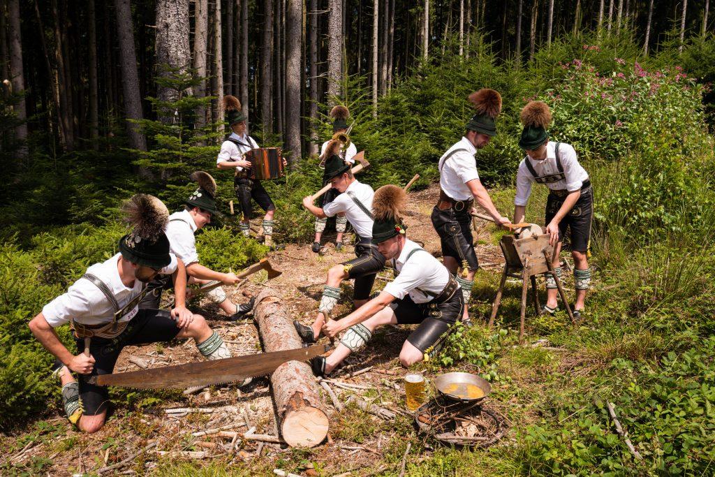 """Die Aktiven Buam beim """"Holzhacker"""" – einem Schuhplatter, der zum """"Holzhacker-Marsch"""" geplattelt wird und Szenen aus dem früheren Holzknecht-Leben darstellt – hier nicht auf der Bühne sondern vor passendem Hintergrund."""